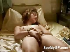 Hot brunette girlfriend fingering her pussy at bed